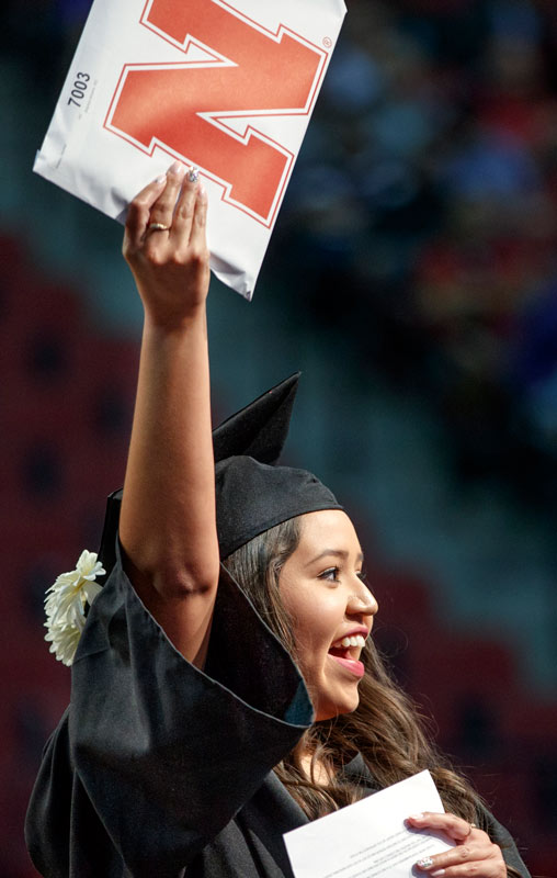 A graduate holds up her diploma at commencement